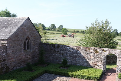 Evening view of the courtyard outbuilding, with hay baying going on in the field.