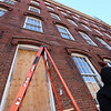 Rebecca Rocheleau of Lowell, a union painter with Tavares LLC, pauses between caulking windows at Boott Mills. They are putting in 360 new windows. (SUN/Julia Malakie)