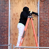 Rebecca Rocheleau of Lowell, a union painter with Tavares LLC, caulks around a window at Boott Mills. They are putting in 360 new windows. (SUN/Julia Malakie)
