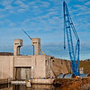 The downstream navigation lock gate at Lower Monumental Dam is being replaced by this enormous crane.  It is 345 feet tall (equal to a 34 story building) and  can lift 1100 tons.  The three curved sections of the new lock gate, visible beneath the crane,  will be inserted after the old gate has been lifted out.  Note the huge stack of concrete counterweights behind the crane.  It used all the adjacent cranes to assemble this huge affair.
