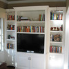 New TV built-in with bookcases and hidden equipment and art lighting illumination
