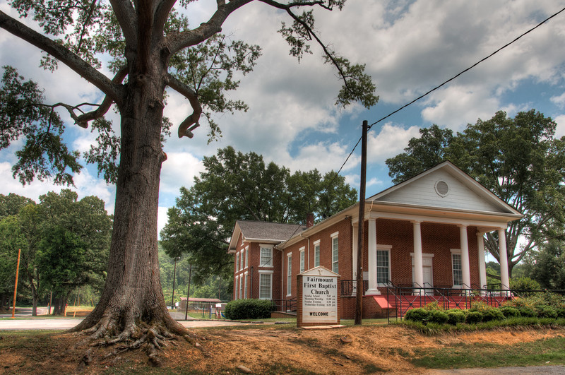 "<h3><strong>Today's Photo:  Fairmount First Baptist</strong></h3> I found this church off the beaten path.  I did not think much of it, because it is kind of a nondescript building.  However,the more I looked at it, the setting began to make itself part of the photo.  Once I backed up and added the old oak tree, it began taking shape.  Looking at the image, I can't decided what I like about it best, the oak tree or the little church in the background.  Read more at the <a href=""http://justshootingmemories.com"">Daily Photography Blog</a> Just Shooting Memories!..."