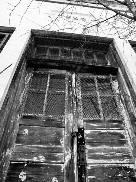 Scary door on a disused building in Fitchburg, MA.  I especially love the bare tree branch.