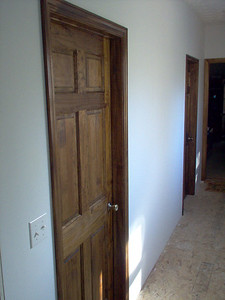 Six panel hardwood doors are stained, varnished, and installed.