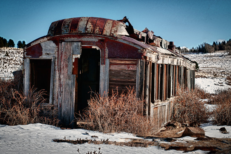 An abandoned rail car sits empty now, probably used for storage or housing in the gold mining town of Victor, Colorado.