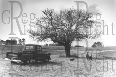Man with his shotgun, dog, and old pickup truck beneath a tree in the meadow. Alabama
