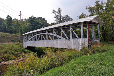 Bowser / Osterburg Covered Bridge (Bedford County, PA)  This bridge is a Burr Truss bridge with horizontal bracing at truss top level. It spans Bob's Creek, just west of Route 869, about 1.5 miles northwest of Osterburg. Bypassed by a steel and concrete bridge in 1973, it is now closed with a cable across the entrance. County owned.  It has vertical boards on the lower 1/3rd of the bridge. It sits on stone and mortar abutments.   PHOTO BY: J. COCHRAN