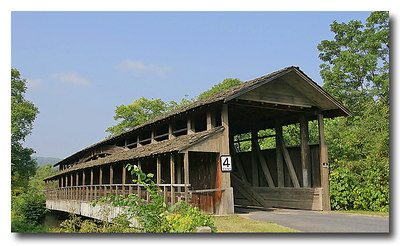 Claycomb Covered Bridge (Bedford County, PA)  This bridge, which stands at the entrance to Old Bedford Village, just north of Bedford, was built in 1880. It was built in Reynoldsdale and was moved to its present location in 1975. A pedestrian walkway was added to the original structure. It is a burr truss design which has been reinforced with steel to support bus traffic that frequents Old Bedford Village. The structure is unpainted. County owned.  The roof is constructed of Cedar shakes and the deck consists of crossboard planks. It sits on poured concrete abutments. The sides are totally enclosed.   PHOTO BY: J. COCHRAN