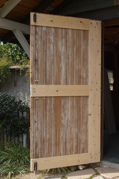 The left door looking towards the vegetable garden in back. The slide latches are probably the original hardware. They anchor the door to the floor and top jamb so the two doors can be latched on the front. When both doors are closed the back side planks form a big figure 8 pattern.