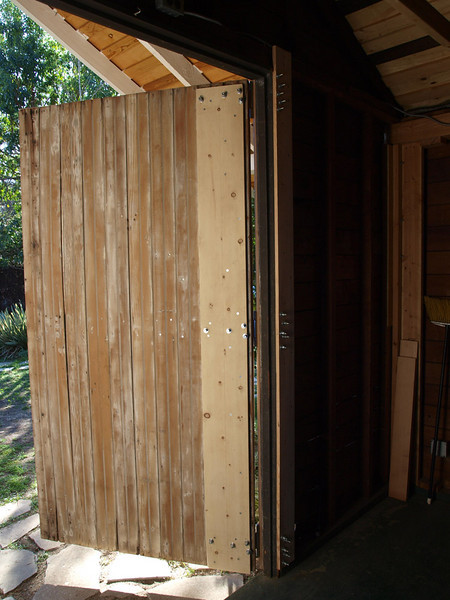 The first door to be restored is placed on the hinges. The jamb was reinforced with new planks of Douglas fir on the jamb - one new facia board on the front and two planks on the back side of the double studs. The back side planks also tie into the double top plate above. The door was full of holes from attempts by previous owners to through-bolt the old hinges. The back side of the door was reinforced with a 1x10 plank of pine screwed to the old door with 18+ large wood screws to tie all three hinges together and connect with the front face boards. Three more 1x8 planks of pine will be added horizontally to the back side to reinforce the door corners and provide a secure backing for bolting hardware and latches.