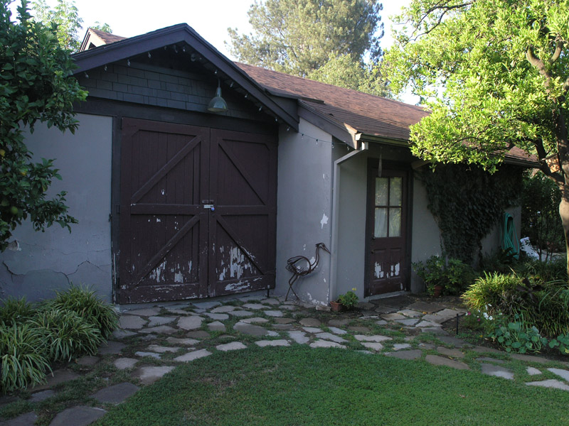 The original 1912 Carriage House on the left and the 1940's garage addition to the right. The door faces south and is weathering badly. In this before image the doors are sagging and won't close completely, leaving a gap at the bottom where dirt blows in and small varmits can enter. The left facia is rotted and the stucco is falling away. This photo was taken before the beam replacement and roof line extension was begun. The right valley ends at a funky diversion flashing that can be seen in that inside corner. That was the only place the roof leaked until just before we started the roof replacement. After the roof was done we began the restoration of these barn doors. OLYMPUS C-8080