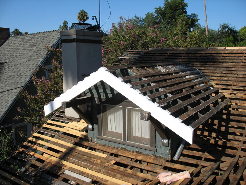New dormer fascia rafters over corbels and chimney with seismic brace collar