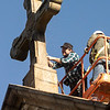 Helming Brothers work to remove a damaged sandstone cross from the roof of the Archabbey Church on Dec. 5, 2019. The cross had been struck by lightning and was deteriorating.