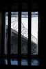 A bleak and dismal view through a prison window. The bars over the window with the only view of coils of barbed wire on a wall is symbolic of the lack of freedom for prisoners.