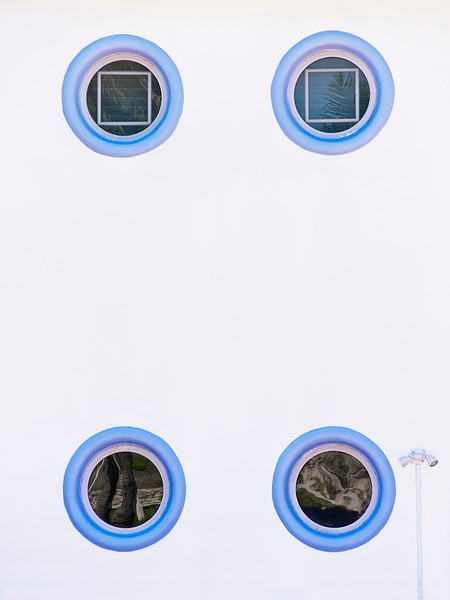 Nice abstract, high key image of four round windows and one floodlight on the exterior wall of an art deco building in South Beach, Miami. Each window has a different reflection.