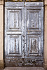 An old door with gray paint that has weathered into a remarkable texture.