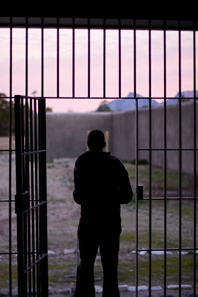 The outline of a man, at sunset, exiting through the iron bars into the prison yard of a jail in South Africa.