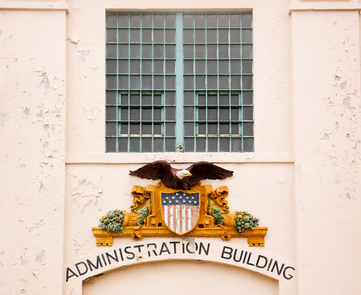 """A bald eagle emblem centered below a window at a prison administration building. The word """"FREE"""" on the flag is an ironic symbol for a penitentiary."""