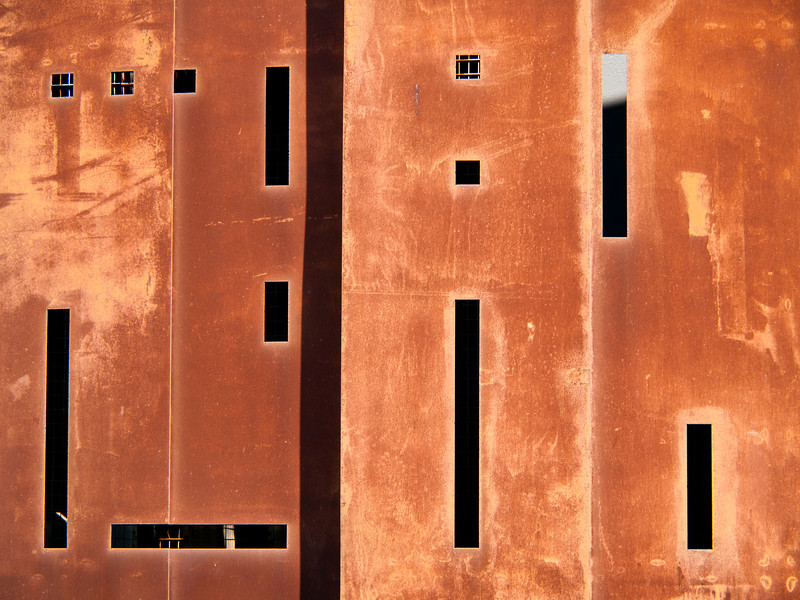 The exterior of a building is a rusty, red color. The black shadows in the windows form an abstract pattern.