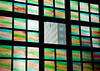 A view of an office building through one clear window surrounded by colored glass panes.