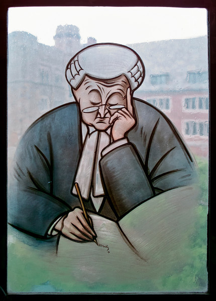 A stained glass image of a lawyer, or perhaps an English barrister, deep in thought who is writing an entry into a journal. In the background, the quadrangle of the law school is visible through the old, stained glass window. The image is framed naturally by the leaded edge of the window.