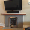 Solid mahogany mantle over large tiles with Shluter edge trim, gave this old fireplace a fresh and stream-lined look.