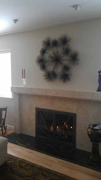 New fireplace with limestone surround and mantle, with custom steel doors in a 1950's ranch, whole house remodel and restoration.