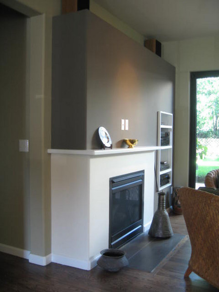 Painted wood mantle and drywall surround for a clean composition.