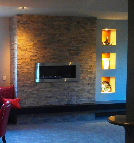 A basement finish included this gas fireplace, floating hearth and inset art niches.
