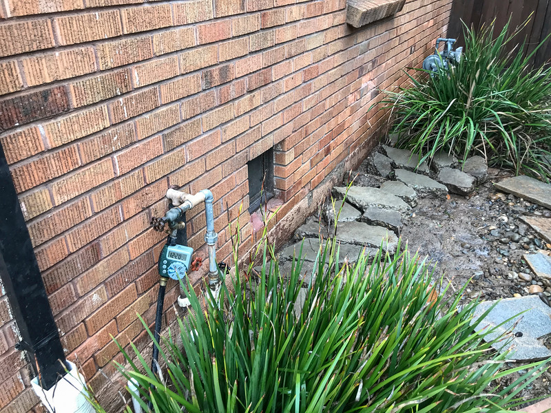 """This is just looking back along the West side or right side of the home.  Under the broken concrete is a 4"""" line running to the back."""