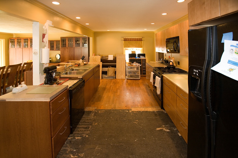 "First view looking to the right as you enter the kitchen.  The difference in flooring indicates where the old kitchen ended.  The hardwood flooring is the old ""piano room"".  The stove used to be right in the center between the new counters (you can see the holes where the gas supply and the electrical wiring came through the floor)."