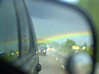 Not a really clear picture but kinda cool. We were driving through a blinding rainstorm and it semed that this huge Rainbow that crossed the sky touched the ground right behind us. I just tried to focus as best I could in the side rear view mirror.  I Took this picture out of the car window going down  Interstate I-20 in Atlanta while running 85+MPH trying to keep up with traffic,,, no I was not driving, I was in the passenger seat...