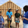 Habitat for Humanity, YouthBuild trainees, CTI, future homeowners, and volunteers raise the second floor gables of a 2-family house being built on Adams Street. From left, future homeowners Hel Pho and her husband Zaw Aung of Lowell, their oldest daughter Phwe Aung, 16, and Kim Trainor of Westford, director of development for Habitat for Humanity of Greater Lowell. (SUN/Julia Malakie)