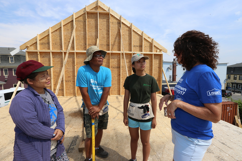 . Habitat for Humanity, YouthBuild trainees, CTI, future homeowners, and volunteers raise the second floor gables of a 2-family house being built on Adams Street. From left, future homeowners Hel Pho and her husband Zaw Aung of Lowell, their oldest daughter Phwe Aung, 16, and Kim Trainor of Westford, director of development for Habitat for Humanity of Greater Lowell. (SUN/Julia Malakie)