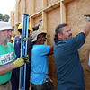 Habitat for Humanity, YouthBuild trainees, CTI, future homeowners, and volunteers raise the second floor gables of a 2-family house being built on Adams Street. From left, Dick Coleman of Westford, future owner Zaw Aung of Lowell, and Angel Roman of Lowell, who works in maintenance at CTI and was one of the extra people brought in to help with lift the walls. (SUN/Julia Malakie)