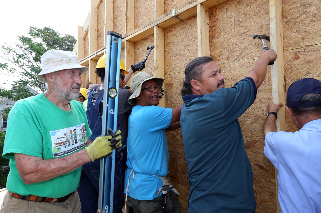 . Habitat for Humanity, YouthBuild trainees, CTI, future homeowners, and volunteers raise the second floor gables of a 2-family house being built on Adams Street. From left, Dick Coleman of Westford, future owner Zaw Aung of Lowell, and Angel Roman of Lowell, who works in maintenance at CTI and was one of the extra people brought in to help with lift the walls. (SUN/Julia Malakie)