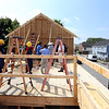 Habitat for Humanity, YouthBuild trainees, CTI, future homeowners, and volunteers raise the second floor gables of a 2-family house being built on Adams Street. (SUN/Julia Malakie)