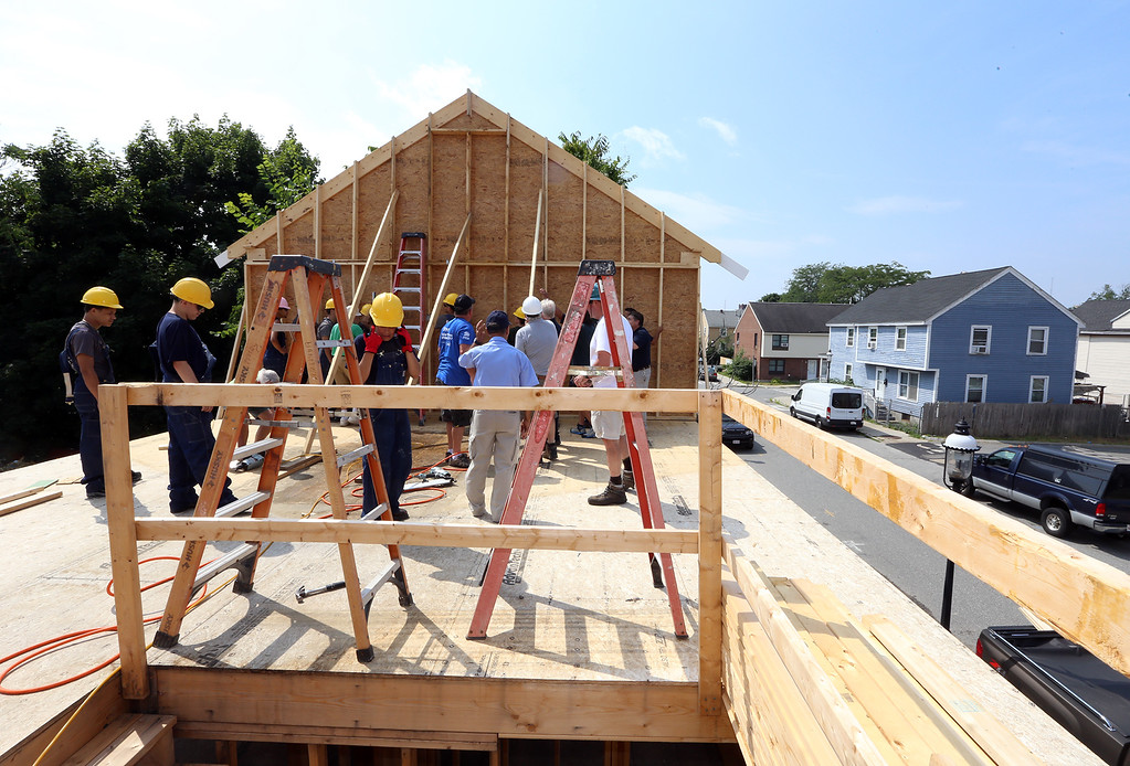 . Habitat for Humanity, YouthBuild trainees, CTI, future homeowners, and volunteers raise the second floor gables of a 2-family house being built on Adams Street. (SUN/Julia Malakie)
