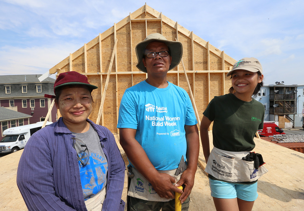 . Habitat for Humanity, YouthBuild trainees, CTI, future homeowners, and volunteers raise the second floor gables of a 2-family house being built on Adams Street. From left, future homeowners Hel Pho and her husband Zaw Aung of Lowell, and their oldest daughter Phwe Aung, 16, who are helping with the construction. (SUN/Julia Malakie)
