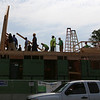 Habitat for Humanity, YouthBuild trainees, CTI, future homeowners, and volunteers raise the second floor gables of a 2-family house being built on Adams Street. They're holding it in place while temporary supports are attached. The back wall will be built on site on the second floor tomorrow. (SUN/Julia Malakie)