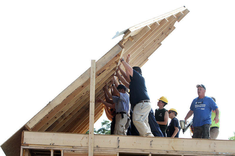 Habitat for Humanity, YouthBuild trainees, CTI, future homeowners, and volunteers raise the second floor gables of a 2-family house being built on Adams Street. The board attached at lower left is what keeps the wall from tipping all the way over before it's secured. (SUN/Julia Malakie)