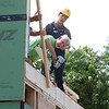 Habitat for Humanity, YouthBuild trainees, CTI, future homeowners, and volunteers raise the second floor gables of a 2-family house being built on Adams Street. Dick Coleman of Westford uses a nail gun to attach temporary supports as Adrian Cellado of Lowell looks on. (SUN/Julia Malakie)