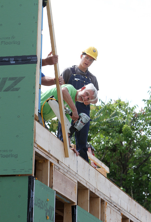 . Habitat for Humanity, YouthBuild trainees, CTI, future homeowners, and volunteers raise the second floor gables of a 2-family house being built on Adams Street. Dick Coleman of Westford uses a nail gun to attach temporary supports as Adrian Cellado of Lowell looks on. (SUN/Julia Malakie)