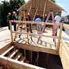 Habitat for Humanity, YouthBuild trainees, CTI, future homeowners, and volunteers raise the second floor gables of a 2-family house being built on Adams Street. These will be the 9th and 10th of ten affordable houses that Habitat committed to build in the Acre. (There are two on Willie Street and six on Rock Street.) (SUN/Julia Malakie)