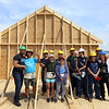 Habitat for Humanity, YouthBuild trainees, CTI, future homeowner Zaw Aung of Lowell, second from left, and volunteers pose for group photo after raising the second floor gables of a 2-family house being built on Adams Street. (SUN/Julia Malakie)
