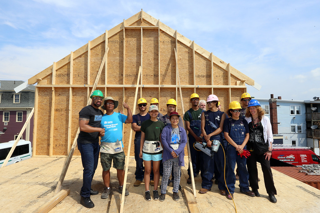 . Habitat for Humanity, YouthBuild trainees, CTI, future homeowner Zaw Aung of Lowell, second from left, and volunteers pose for group photo after raising the second floor gables of a 2-family house being built on Adams Street. (SUN/Julia Malakie)