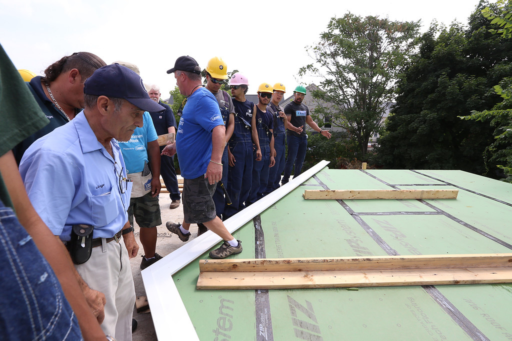 . Habitat for Humanity, YouthBuild trainees, CTI, future homeowners, and volunteers prepare to raise a second floor gable of a 2-family house being built on Adams Street. (SUN/Julia Malakie)