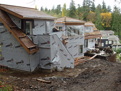 The building to the left is the garage (exercise room on the top.)  the next area you see is the stair way  and then the last is the livingroom with my office on top. The black house below is our neighbors.  This time next year you will not recognize this side yard.