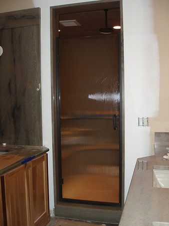 The reed glass shower door is just being installed, to the left is the jetted Japanese sitting tub, to the right the sink area.
