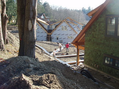 "This is the corner of the Garage, with the exercise room above, the men are working on the concrete ""ribbons"" for the driveway.  The ""grey"" house is nearly half way finished... we know they will be great neighbors."